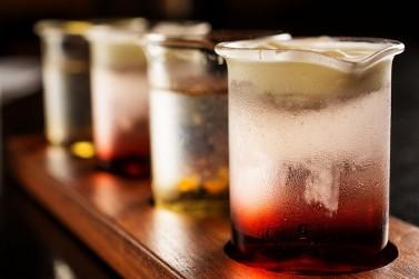 """Sequência de shots do Caverna """"Thelma & Louise"""" com chantilly de amaretto, licor de cassis e vodka, tequila prata licor de damasco e duas gotas de tabasco"""