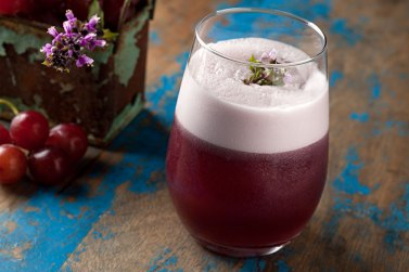 Drinque Rojo com pisco, uva bordo, manjericão e cítricos